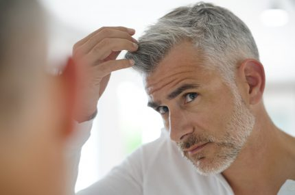 siwy mężczyzna przeglądający się w lustrze